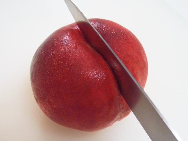 桃の割れ目に沿って包丁を入れる